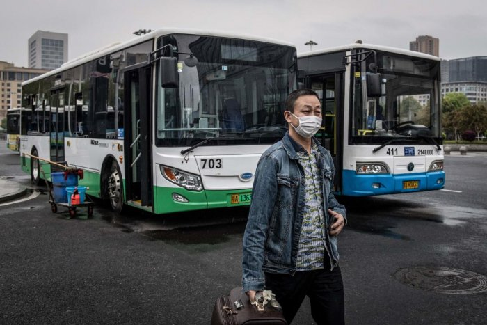 A man gets out of a bus in Wuhan in China's central Hubei province on March 25, 2020, after the public transportation partly resumed in the city. Credit: AFP Photo