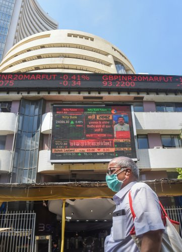 A man wears a mask and walks past the BSE building, as the Sensex crashed by nearly 3000 points, in Mumbai. (PTI Photo)