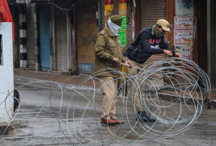 Security personnel put concertina wires to block a road during lockdown in the wake of coronavirus outbreak, in Jammu. (PTI Photo)
