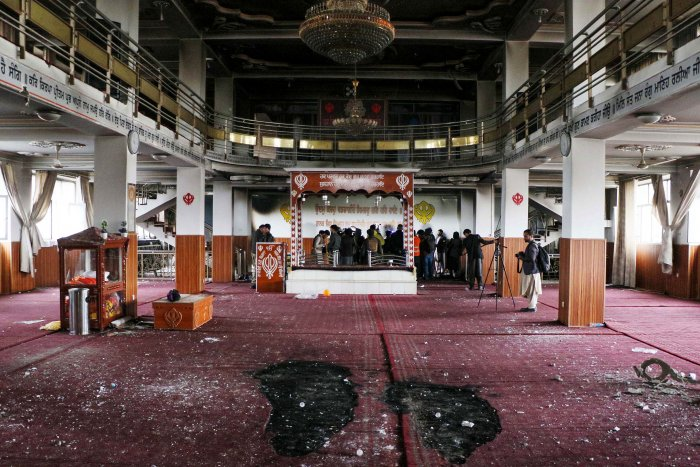 Security personnel inspect a damaged Sikh-Hindu Temple alongside with media representatives following a gun attack in Kabul on March 25, 2020. (Credit: AFP Photo)