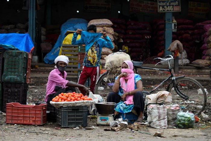 Vegetable vendors with their faces covered wait for customers during a government-imposed nationwide lockdown as a preventive measure against the COVID-19. (Credit: AFP)