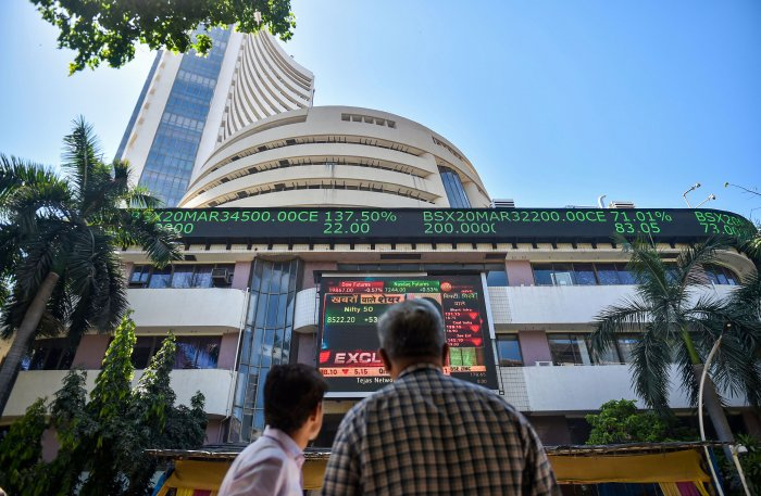 People watch the Sensex on a screen outside Bombay Stock Exchange (BSE) in Mumbai, Thursday, March 19, 2020. Equity benchmark Sensex ended 581 points lower in a highly volatile session. (PTI Photo)