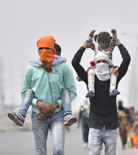A group of migrant workers walk to their villages amid the nationwide complete lockdown, on the NH24. (Credit: PTI)