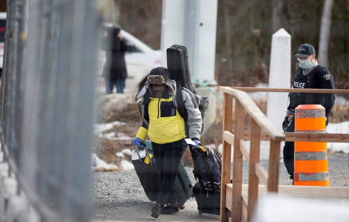 FILE PHOTO: An asylum seeker crosses the border from New York into Canada followed by a Royal Canadian Mounted Police (RCMP) officer at Roxham Road in Hemmingford, Quebec, Canada. (Credit: Reuters)