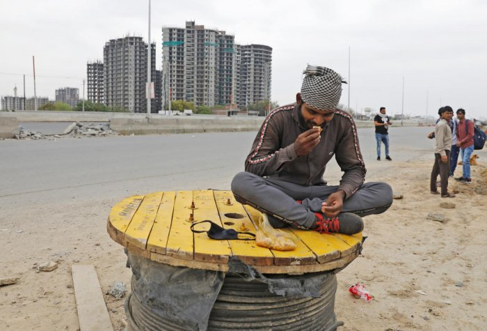 A migrant worker eats food offered by local residents on a highway as he and others are returning to their villages, after India ordered a 21-day nationwide lockdown to limit the spreading of coronavirus disease, in Ghaziabad, on the outskirts of New Delh