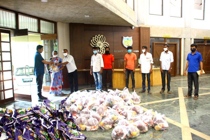 Rev Fr Rohith D'Costa, assistant director of St Joseph Engineering College, hands over a kit to the representatives of Neermarga Gram Panchayat.
