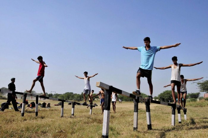 Amritsar: Candidates walk on balance beams during their physical fitness test at an Indian Army recruitment rally at Khasa near Amritsar on Thursday. PTI Photo