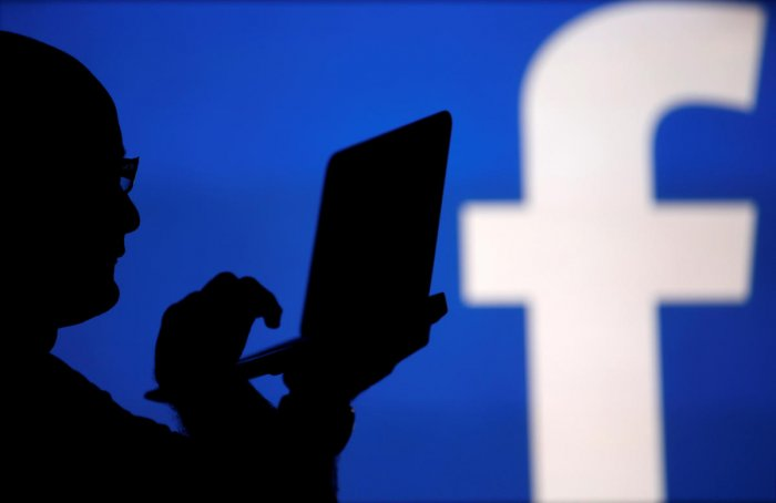 FILE PHOTO: A man is silhouetted against a video screen with an Facebook logo as he poses with a laptop in this photo illustration taken in the central Bosnian town of Zenica, August 14, 2013. REUTERS/Dado Ruvic/File Photo