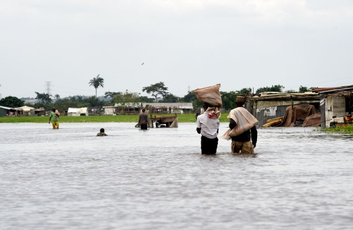 eople carry their belonging on their heads while they walk on a flooded road following heavy rain downpour in Wawa in Ogun State southwest Nigeria. (AFP Photo)