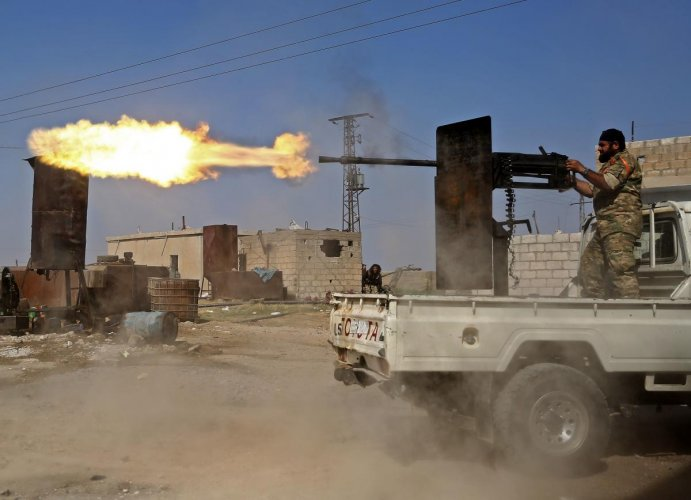 A Turkish-baked Syrian fighter fires during clashes in the border town of Ras al-Ain on October 13, 2019, as Turkey and its allies continue their assault on Kurdish-held border towns in northeastern Syria. (Photo by Nazeer Al-khatib / AFP)