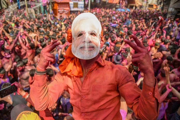 BJP supporter wears a mask of Prime Minister Narendra Modi during Holi festival celebration, in Allahabad, on Friday. PTI