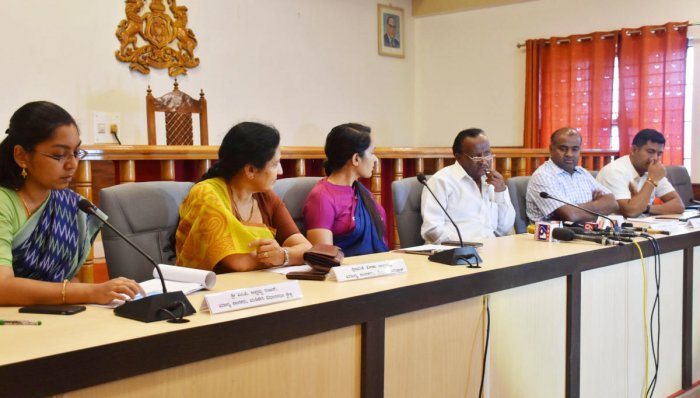Housing Minister M T B Nagaraj (third from right) speaks to reporters in Madikeri on Saturday.