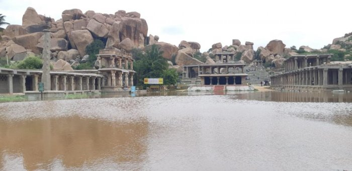 A swollen Tungabhadra River inundated the Rathabeedhi located in front of Basava Mantapa in Hampi on Sunday. DH Photo/Shashikanth Shembelli