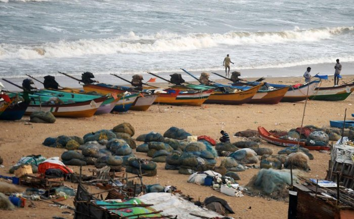 Indian fishermen stand along a beach (AFP Photo)