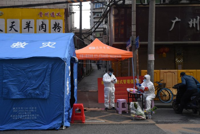 Workers in protective suits are seen at a checkpoint for registration and body temperature measurement in Wuhan
