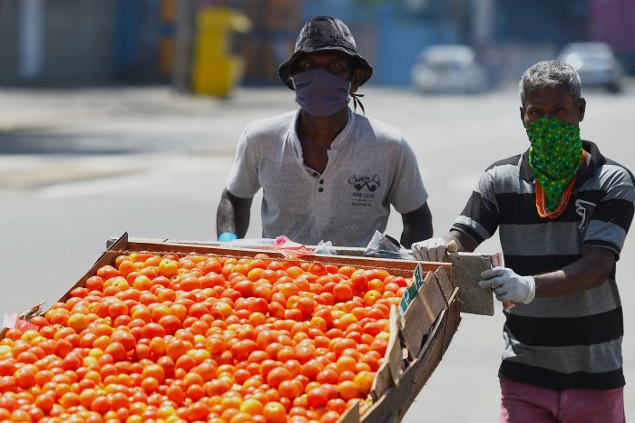 Vendors wearing facemasks look for customers along a deserted street in Colombo. (AFP Photo)