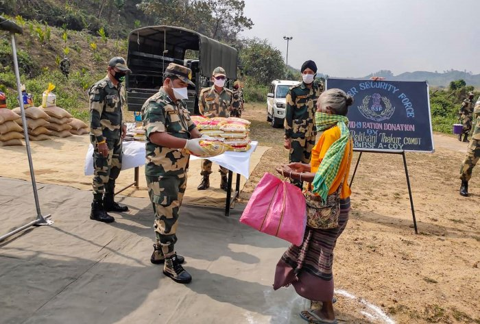 Officials of 43 Battalion of Border Security Force (BSF) distribute ration amongst the needy people during the nationwide lockdown, imposed in the wake of coronavirus pandemic. (Credit: PTI Photo)