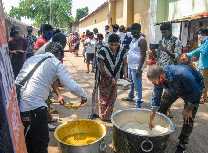 Volunteers distribute free meals among needy people during the nationwide lockdown, in wake of the coronavirus pandemic, in Bhubaneswar. (Credit: PTI Photo)
