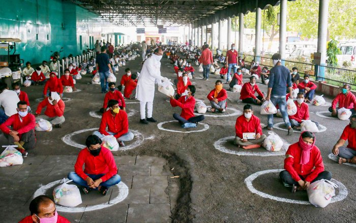 Vishwas Sarang, BJP MLA from Narel, distributes food and essential items to railway porters at a railway station, during the nationwide lockdown imposed to curb the spread of coronavirus. (PTI Photo)