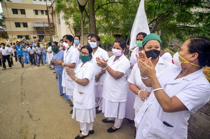 Medics clap as a patient who recovered from COVID-19 is discharged from a hospital, during the nationwide lockdown to curb the spread of coronavirus, in Agartala. (Credit: PTI Photo)