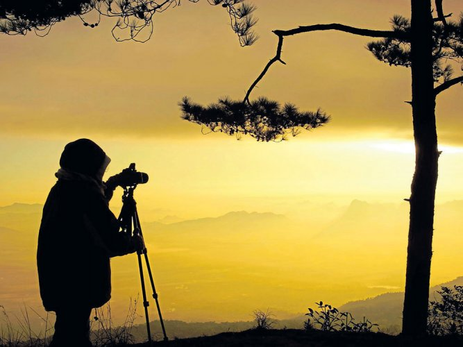 An image of a photographer clicking pictures. Image for representation