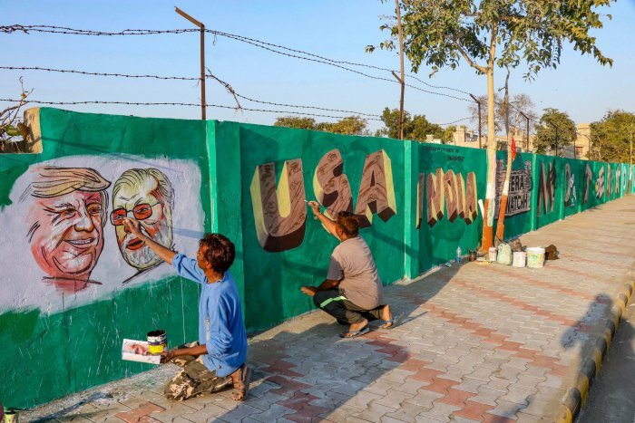 A man applies finishing touches to paintings of U.S. President Donald Trump and India's Prime Minister Narendra Modi on a wall as part of a beautification along a route that Trump and Modi will be taking during Trump's upcoming visit, in Ahmedabad. (PTI Photo)