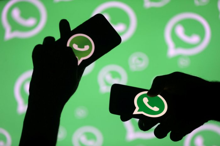 Men pose with smartphones in front of the displayed Whatsapp logo in this illustration. Photo by REUTERS