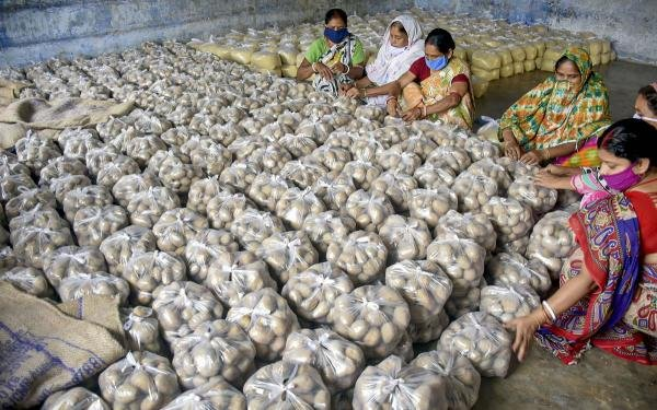 School staff prepares food packets to distribute among guardians of students as mid-day meal at a school in Murshidabad. (Credit: PTI Photo)