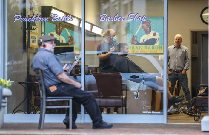 Barber and owner of Chris Edwards wears a mask and cuts the hair of customer as others wait at Peachtree Battle Barber Shop in Atlanta. AP/PTI