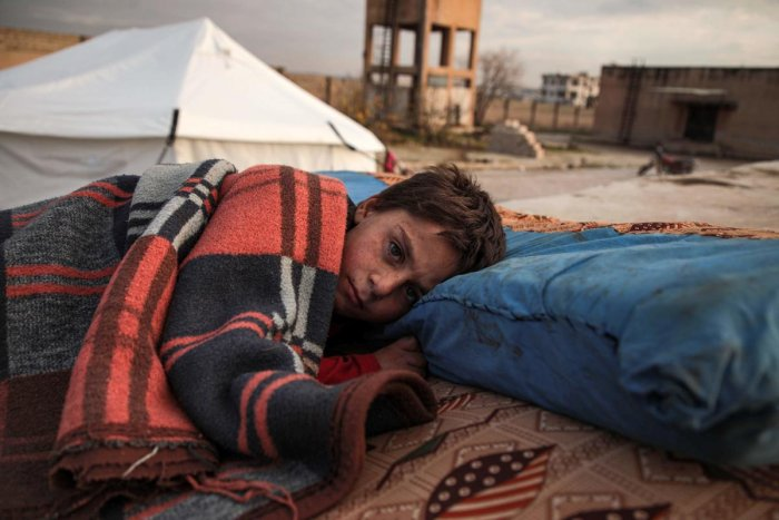 A Syrian child, one of those who fled from government forces' advance on Maaret al-Numan in the south of Idlib prvoince, sleeps on a futon in the open at a camp for the displaced near the town of Dana in the province's north near the border with Turkey, on December 27, 2019. (Photo by Aaref WATAD / AFP)