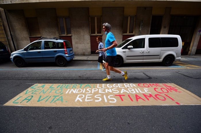 """People jog past a banner on a road which reads """"Freedom, light as the wind, indispensable as life, let's resist!"""". (Reuters Photo)"""