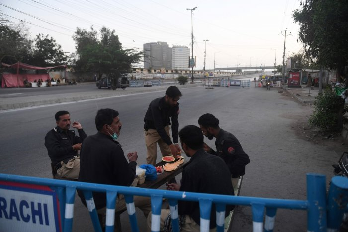 Policemen pray before breaking their fast at a checkpoint on the first day of the Islamic holy month of Ramadan under a government-imposed nationwide lockdown as a preventive measure against the spread of the COVID-19 coronavirus in Karachi. (AFP Photo)