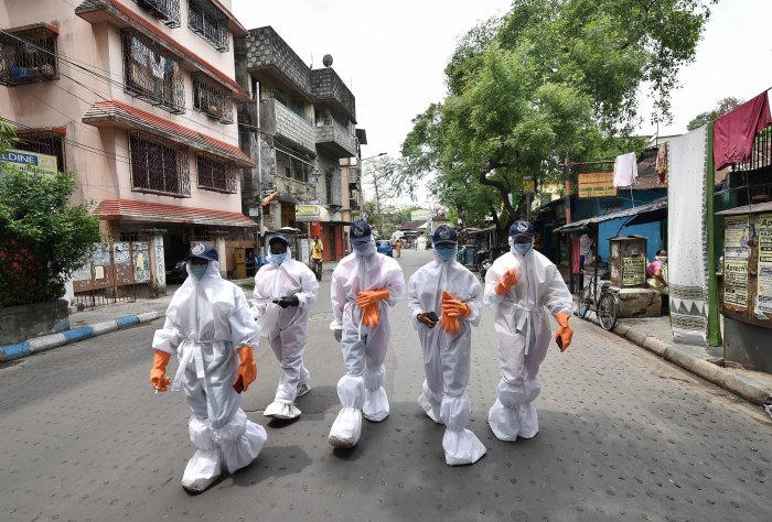 Health workers wearing protective suits walk in a locality during their door-to-door surveillance to detect COVID-19 cases. (PTI Photo)