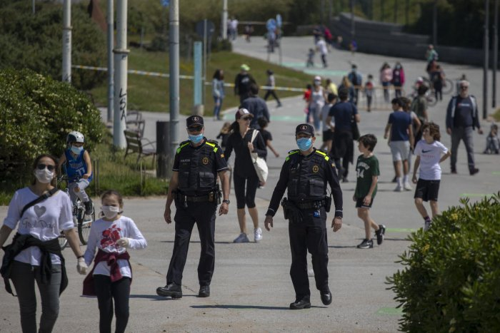 Catalan police officers patrol as families with their children walk along a boulevard in Barcelona, Spain, Sunday, April 26, 2020 as the lockdown to combat the spread of coronavirus continues. Credit: AP Photo