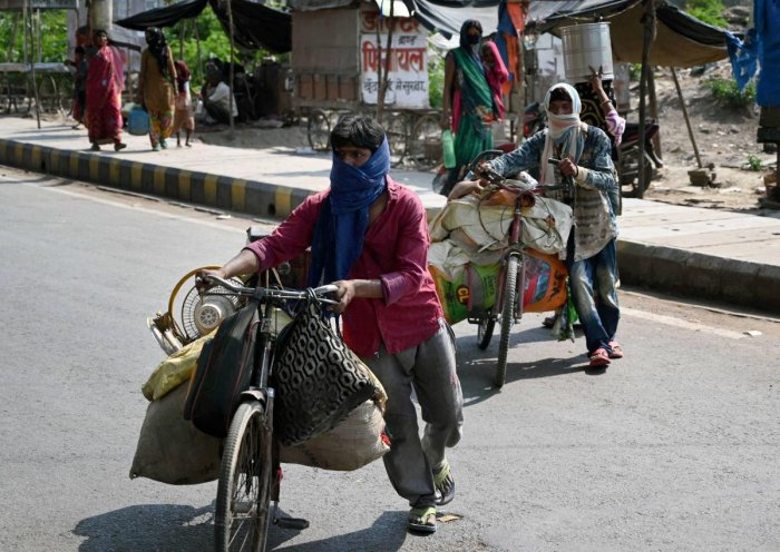 Migrant workers with their belongings walk towards their native place during a government-imposed nationwide lockdown as a preventive measure against the coronavirus, in Prayagraj, Saturday, April 25, 2020. (PTI Photo)