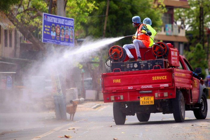 Firefighters spray disinfectant on a street after a person was found positive with COVID-19 at Rail Museum Shelter home during a government-imposed nationwide lockdown as a preventive measure against the coronavirus pandemic, in Ajmer, Saturday, April 18, 2020. Credit: PTI Photo