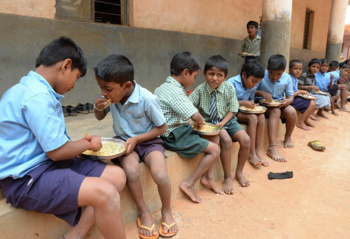 A file picture of children having mid-day meals in schools. Hundreds of schools in Udupi district have not been able to cook mid-day meals due to water scarcity.