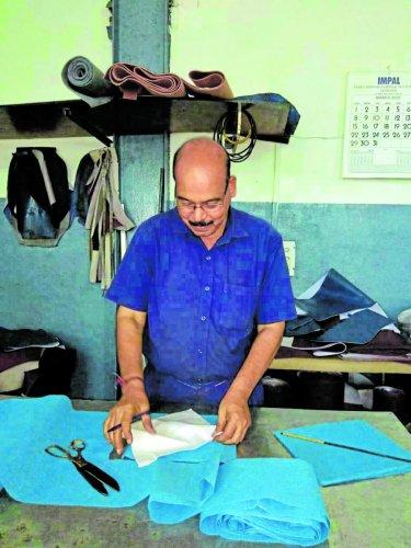 A mechanic stitches masks at KSRTC Mangaluru division's workshop in Mangaluru on Friday.