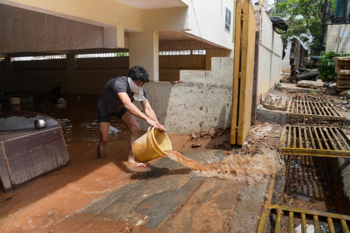 A resident flushes out dirty rainwater from the basement of the Deccan Heritage apartment in ITI Layout, New BEL Road, in Bengaluru on Friday. DH PHOTO/B H SHIVAKUMAR