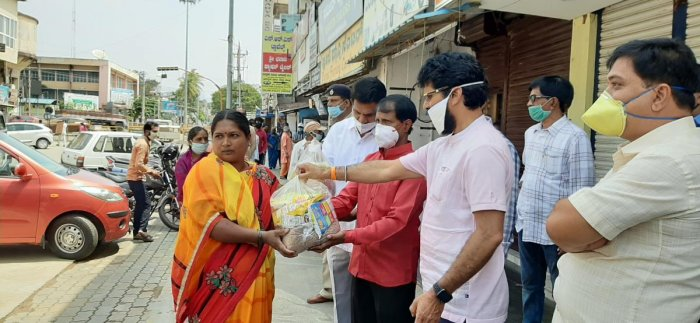 District In-charge Minister C T Ravi distributes grocery kits to members of Gondali community at M G Road in Chikkamagaluru.