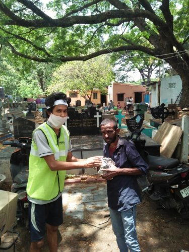 A member of the Covid Biker Relief Squad gives a food packet to a graveyard worker. (R) Members of the squad. SPECIAL ARRANGEMENT