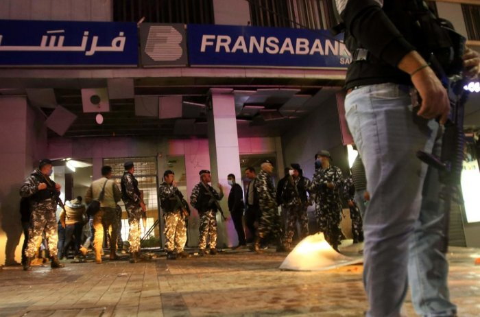 Lebanese security forces inspect the entrance of a Fransabank branch in Lebanon's southern city of Sidon on April 25, 2020, after unknown assailants targeted the bank entrance with an explosive device.