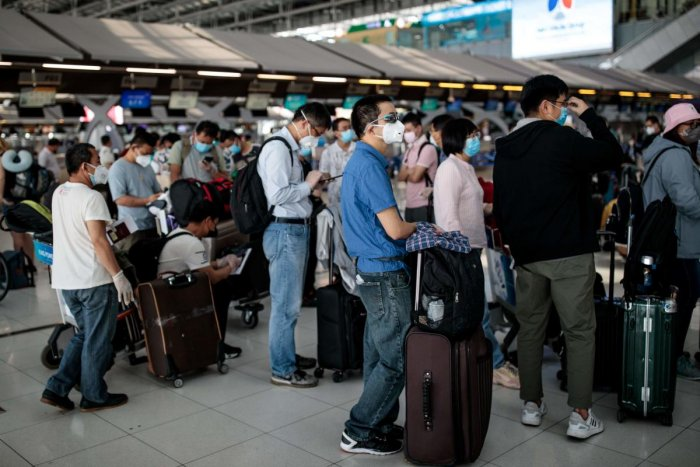 People wearing face masks wait in check-in lines as airlines cancelled dozens of flights amid concerns over the spread of the COVID-19 coronavirus at Suvarnabhumi Airport in Bangkok on March 25, 2020.