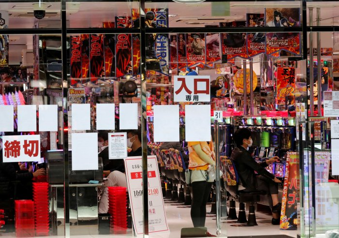 Visitors play pachinko, a Japanese form of legal gambling, at a pachinko parlour, after the government announced nationwide state of emergency following the coronavirus disease (COVID-19) outbreak, in Tokyo. (Credit: Reuters)