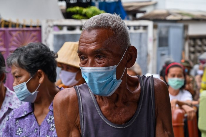 Elderly people line up for food and cash donations in a Bangkok district. (AFP)