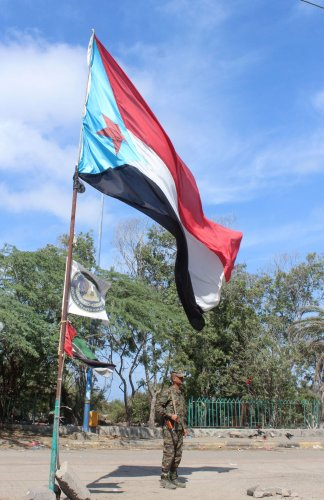 A fighter with Yemen's Southern Transitional Council (STC) stands guard beneath a separatist flag (the old flag of South Yemen) in the southern city of Aden. (AFP photo)