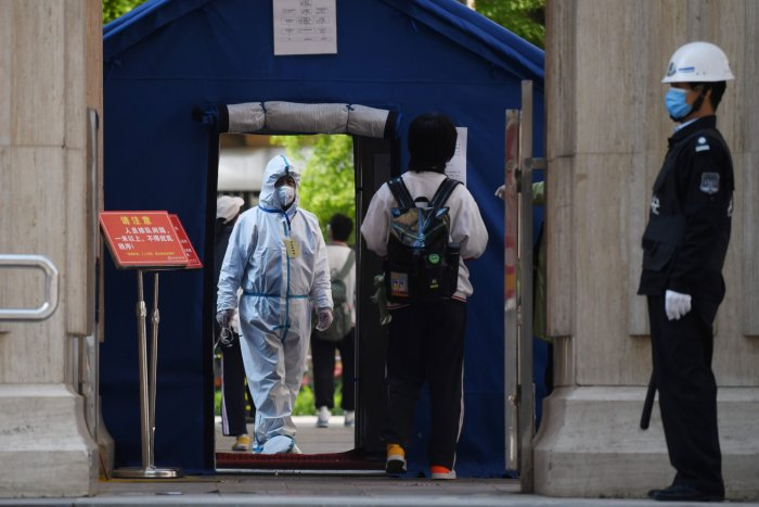 An official in a hazmat suit waits inside a high school entrance as a student arrives in Beijing. (AFP Photo)