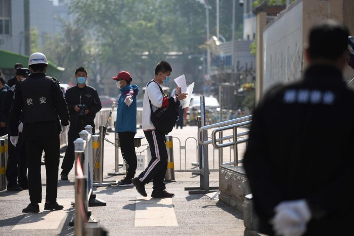 A student walks past police and officials as he arrives at a high school in Beijing. (AFP Photo)