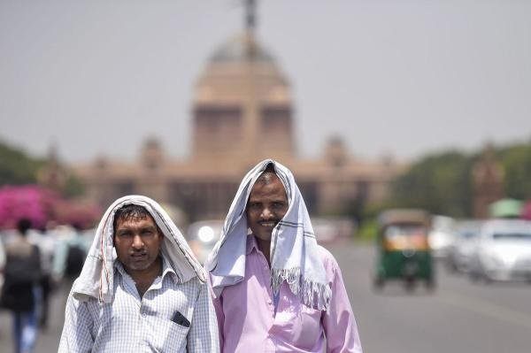Pedestrians cover their heads to shield from the scorching sun, on a hot summer day, in New Delhi, Monday, June 10, 2019. (PTI Photo/Atul Yadav)