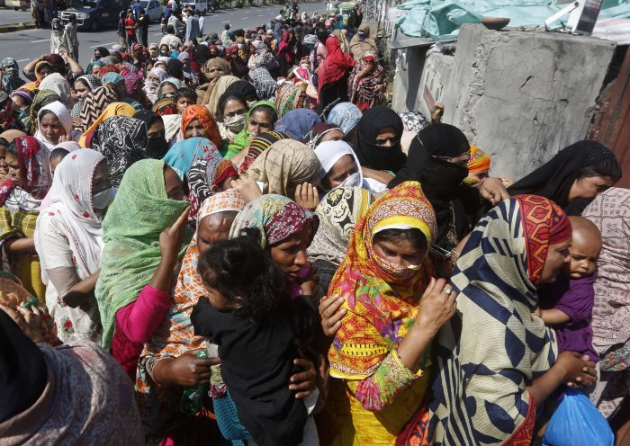 People wait to receive food assistance ahead of the Muslim fasting month of Ramadan, during a government-imposed nationwide lockdown to help contain the spread of the coronavirus. (AP Photo)